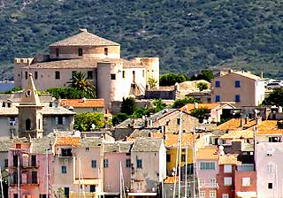 Rooftops and pastel coloured houses below Saint Florent citadel